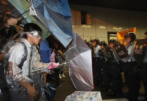 A student protester in his school uniform stands off with riot police inside a vehicle tunnel as pro-democracy protesters stormed in to block a road leading to the financial Central district in Hong Kong October 14, 2014. (REUTERS/Stringer)