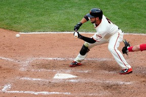 San Francisco Giants centre fielder Gregor Blanco hits a sacrifice bunt that let to the game winning run in the 10th inning against the St. Louis Cardinals during Game 3 of the 2014 NLCS at AT&T Park on October 14, 2014. (Ed Szczepanski/USA TODAY Sports)