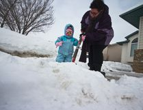 Shayne-Lynn Green, 2, helps her mother Darlene shovel snow off their driveway last winter. A new snow clearing strategy is meant to expedite and simplify this year's winter road care in the City of Grande Prairie, but some of the work is being left to homeowners. TOM BATEMAN/DAILY HERALD-TRIBUNE/QMI AGENCY