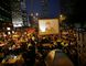 Pro-democracy protesters watch formal talks between student protest leaders and city officials on a video screen near the government headquarters in Hong Kong Oct. 21, 2014. REUTERS/CARLOS BARRIA