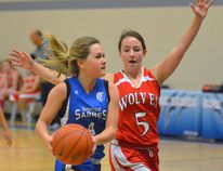 Simcoe Sabres' Haley Moulton (left) attempts for a basketball while Danielle Hiltz of the Waterford Wolves blocks during the third quarter of Tuesday's senior girls basketball game at Simcoe Composite School. Simcoe defeated Waterford 56-9. (EDDIE CHAU Simcoe Reformer)