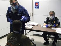 U.S. Coast Guard Health Technician Nathan Wallenmeyer (L) and Customs Border Protection (CBP) Supervisor Sam Ko conduct pre-screening measures on a passenger arriving from Sierra Leone at O'Hare International Airport's Terminal 5 in Chicago, in this handout picture taken October 16, 2014. (REUTERS/U.S. Customs Border Protection/Melissa Maraj/Handout via Reuters)