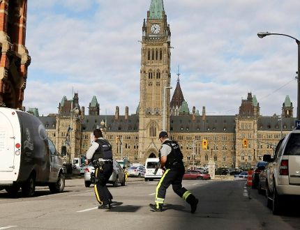 Armed RCMP officers race across a street on Parliament Hill following a shooting incident in Ottawa October 22, 2014. A Canadian soldier was shot at the Canadian War Memorial and a shooter was seen running towards the nearby parliament buildings, where more shots were fired, according to media and eyewitn