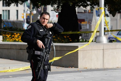 A police officer patrols the scene near the Canada War Memorial following a shooting incident in Ottawa October 22, 2014.  A Canadian soldier was shot at the Canadian War Memorial and a shooter was seen running towards the nearby parliament buildings, where more shots were fired, according to media and eyewitness reports.        REUTERS/Chris Wattie