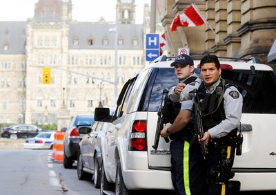 Armed RCMP officers guard access to Parliament Hilll following a shooting incident in Ottawa October 22, 2014.  A Canadian soldier was shot at the Canadian War Memorial and a shooter was seen running towards the nearby parliament buildings, where more shots were fired, according to media and eyewitness reports.       REUTERS/Chris Wattie