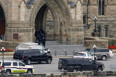 Armed RCMP officers head in to Centre Block on Parliament Hilll following a shooting incident in Ottawa October 22, 2014.  A Canadian soldier was shot at the Canadian War Memorial and a shooter was seen running towards the nearby parliament buildings, where more shots were fired, according to media and eyewitness reports.        REUTERS/Chris Wattie
