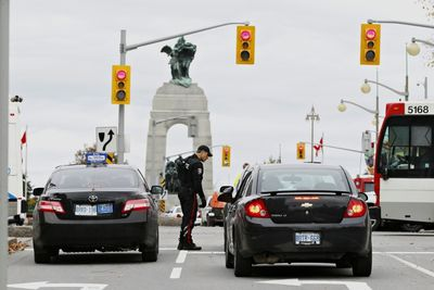 Police stop cars approaching Parliament Hill in Ottawa on Wednesday Oct. 22, 2014. An arrest has been made after at least one person was shot in a hail of gunfire on Parliament Hill and the nearby cenotaph. Errol McGilhon/Ottawa Sun/QMI Agency