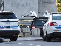Forensic workers work the scene where a solider was shot and killed at the National War Memorial in Ottawa on Wednesday, Oct.