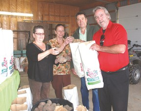 Ruth Leatham, left, Jan Vander, head chef at Beattie Haven, Richard Leatham, and Glenn Degraw, administrator at Beattie Haven, show off bags of potatoes the Leathams and Dixon Feed Service in West Lorne donated to Beattie Haven. The potatoes were grown this year from surplus seed potatoes.