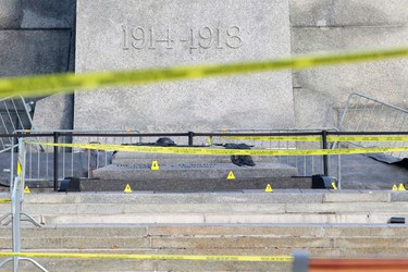Evidence markers are seen on the ground at the Canadian War Memorial in downtown Ottawa October 23, 2014. A gunman attacked Canada's parliament on Wednesday, with gunfire erupting near a room where Prime Minister Stephen Harper was speaking, and a soldier was fatally shot at the nearby war memorial, jolting the Canadian capital. REUTERS/Blair Gable (CANADA - Tags: POLITICS MILITARY CRIME LAW)