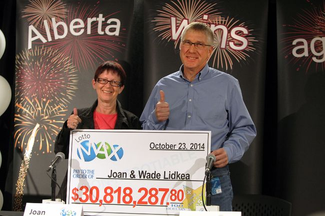 New millionaires Joan and Wade Lidkea holds their cheque for $30,818,287.80 at the Alberta Gaming & Liquor Commission office in St Albert, Alberta on Thursday, October 23, 2014.  Perry Mah/Edmonton Sun