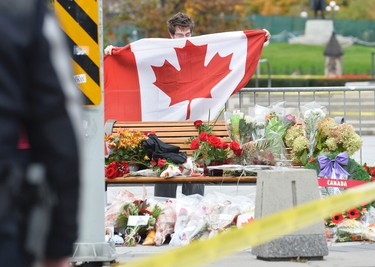 A man lays a Canadian Flag at the National War Memorial in Ottawa on Thursday, Oct. 23, 2014, where a solider was shot and killed in Ottawa. Matthew Usherwood/ QMI Agency