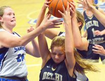 Delhi's Kassidy Deming (centre) fights to keep the basketball in her grasp as members of the Simcoe Sabres surround her. On Thursday, the Delhi Raiders defeated the Simcoe Sabres 60-48. (EDDIE CHAU Simcoe Reformer)
