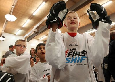 Braden Giese, 9, tries on new hockey gloves during The First Shift welcome event at the Central Lions Senior Citizens Centre, 11113 - 113 St., in Edmonton Alta., on Thursday Oct. 23, 2014. The First Shift, an initiative between Bauer hockey equipment and Hockey Canada, is giving 45 local kids a chance to play hockey for the first time, outfitting them in head-to-toe gear before enrolling them in specially designed 6-week coaching sessions. David Bloom/Edmonton Sun/QMI Agency