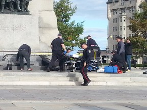 Photos of the week - Emergency crews attend to a soldier who was shot while standing guard at Ottawa's War Memorial near Parliament Hill in Ottawa on Wednesday Oct. 22, 2014. An arrest has been made after at least one person was shot in a hail of gunfire on Parliament Hill and the nearby cenotaph. Jon Willing/Ottawa Sun/QMI Agency