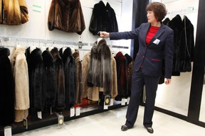 A sales woman displays a mink coat to customers at a shopping mall in Shanghai, April 4, 2013. (REUTERS)