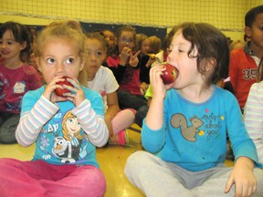 Kaliyah Formosa and Hailey Brooks, kindergarten students at St. Joseph Catholic School in Chatham, bite into some shiny apples as part of the Great Big Crunch on Oct. 23. Over 14,000 apples were delivered to more than 40 schools for the event.