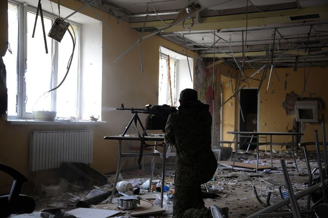 A pro-Russian separatist soldier fires through a window at the Donetsk's Sergey Prokofiev international airport during a shelling between Ukrainian army forces and pro-Russian separatist soldiers on October 16, 2014. (AFP PHOTO/DOMINIQUE FAGET)