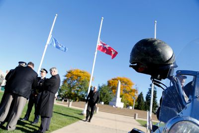 A soldier's helmet rests on the handle of a motorcycle parked at the Trenton Cenotaph on October 24, 2014 during a ceremony to honour WO Patrice Vincent and Cpl. Nathan Cirillo. (Emily Mountney-Lessard/The Intelligencer/QMI Agency)