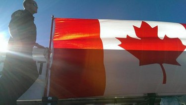 A Canadian flag is held up in Trenton, Ont., as the Nathan Cirillo motorcade passed through on October 24, 2014. (Jerome Lessard/QMI Agency)