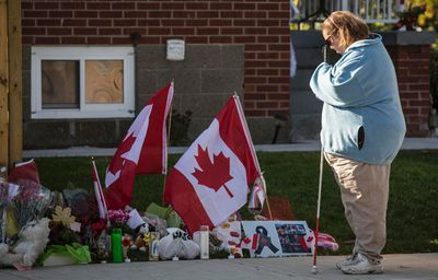 A woman pays respects at a makeshift memorial in honour of Cpl. Nathan Cirillo, outside his family's Hamilton home on October 24, 2014. Cirillo was gunned down in a terror attack at the Canada War Memorial in Ottawa two days earlier. (REUTERS)