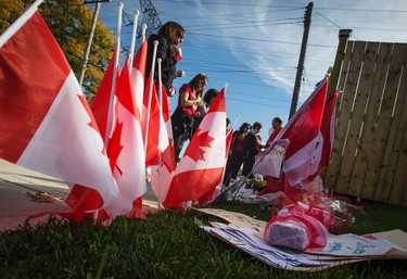 Workers from the St. Eugene Catholic Elementary School, where Cpl. Nathan Cirillo's son is enrolled, pay respects at a makeshift memorial in honour of Cpl. Cirillo, outside the family home in Hamilton, October 24, 2014.  Cirillo was killed during a shooting incident at the Canada War Memorial in Ottawa on October 22. Canada vowed on Friday to toughen laws against terrorism as an opinion poll showed a majority of Canadians lacked confidence in their security services' ability to deter homegrown radicals who struck twice in the past week.   REUTERS/Mark Blinch