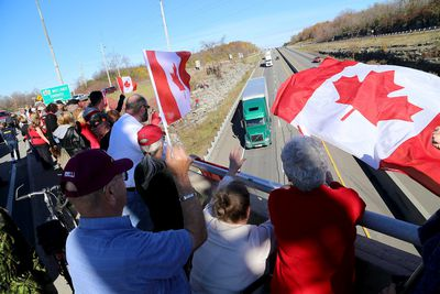 Members of the public along with military members stand along the Hwy. 15 overpass in Kingston on Friday October 24 2014 to pay their respects to Cpl. Nathan Cirillo who's body was being transferred from Ottawa to Hamilton with a police escort. (IAN MACALPINE-KINGSTON WHIG-STANDARD/QMI AGENCY