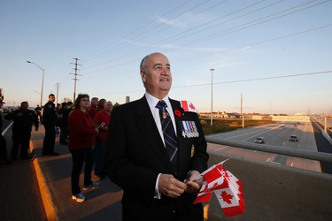 Minister of Veterans Affairs Julian Fantino handed out  Canadian flags on the Jane Street overpass over Highway 407,  and gave a large flag to firefighters after the procession of Cpl. Nathan Cirillo passed by ,  on Friday October 24, 2014. Stan Behal/Toronto Sun/QMI Agency