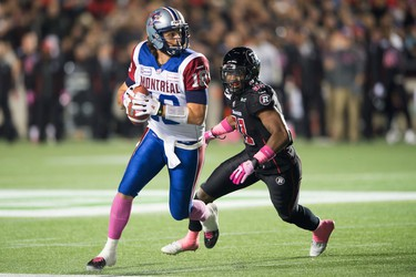 Montreal Alouettes' Jean-Jonathan Crompton runs with the ball with Ottawa Redblacks' Jasper Simmons chasing during the second quarter at TD Place in Ottawa on Friday Oct. 23, 2014. Marc DesRosiers/QMI Agency