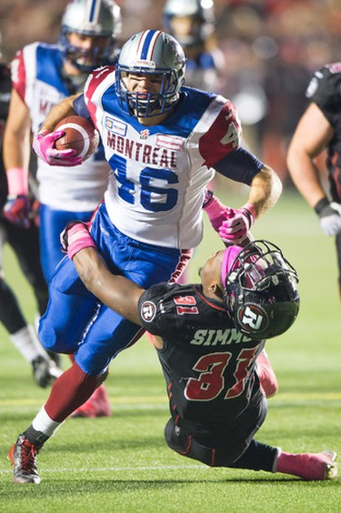 Montreal Alouettes' Jean-Christophe Beaulieu runs with the ball past Ottawa Redblacks' Jasper Simmons in the second quarter at TD Place in Ottawa on Friday Oct. 23, 2014. Marc DesRosiers/QMI Agency