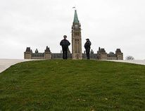 Royal Canadian Mounted Police officers stand guard on Parliament Hill in Ottawa October 23, 2014. A gunma