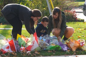 Cpl. Nathan Cirillo's son, Marcus, explored some of the toys Saturday that were left for home at memorial set up outside the family's Hamilton home. (Chris Doucette/Toronto Sun)