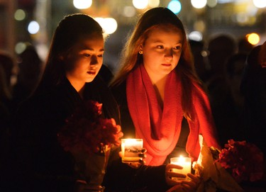 Morgan Leung (L) and Erin Millward (R) hold candles during a candle light vigil at the National War Memorial in Ottawa to show her respect to Cpl Nathan Cirillo on Saturday Oct. 25, 2014. Cirillo was shot and killed earlier this week in Ottawa on Wednesday, Oct. 22, 2014. Matthew Usherwood/ Ottawa Sun