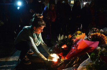 13 year old Chloee Nantel lays a candle during a candle light vigil at the National War Memorial in Ottawa to show her respect to Cpl Nathan Cirillo on Saturday Oct. 25, 2014. Cirillo was shot and killed earlier this week in Ottawa on Wednesday, Oct. 22, 2014. Matthew Usherwood/ Ottawa Sun