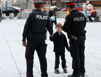 Avery Bruce, 5, shakes hands with two Ottawa Police officers keeping watch at the National War Memorial Saturday, Oct. 26, 2014 where people continued to stop to pay their respects and lay flowers and other items at the monument. (Chris Hofley/QMI Agency)