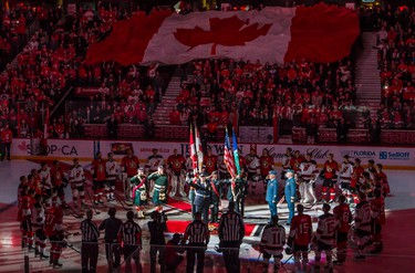 Ottawa Senators' players and New Jersey Devils', along with game officials and representatives of Canada's military, stand together at centre ice as Lyndon Slewidge leads the sold out crowd at Canadian Tire Centre in the singing of O' Canada prior to the NHL hockey game at the Canadian Tire Centre in Ottawa, Ontario on Saturday October 25, 2014. The teams were honouring fallen soldier Cpl. Nathan Cirillo who was gunned down at the National War memorial on October 22. Errol McGihon/Ottawa Sun/QMI Agency