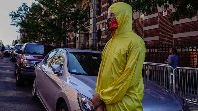 A man wearing personal protective equipment (PPE) as a Halloween costume, stands in front of the building where Dr. Craig Spencer lives in New York October 25, 2014.   REUTERS/Eduardo Munoz