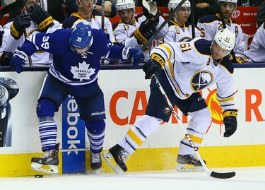 Matt Frattin of the Toronto Maple Leafs gets around Andre Benoit of the Buffalo Sabres during NHL action at the Air Canada Centre in Toronto on Tuesday October 28, 2014. Dave Abel/Toronto Sun/QMI Agency