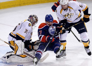 The Edmonton Oilers' Boyd Gordon (27) is upended by the Nashville Predators' Shea Weber (6) in front of goalie Pekka Rinne (35) during second period NHL action at Rexall Place, in Edmonton Alta., on Wednesday Oct. 29, 2014. David Bloom/Edmonton Sun/QMI Agency