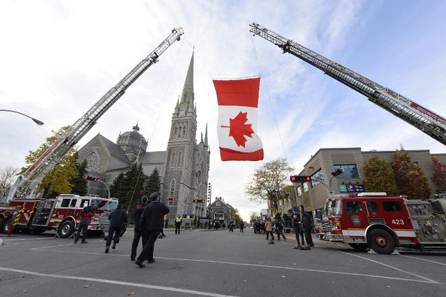 A Canadian flag is raised at the funeral for Warrant Officer Patrice Vincent in Longueuil, Quebec November 1, 2014. (JOEL LEMAY/QMI AGENCY)