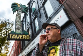 Howard Dover, organizer of the 25th annual medical marijuana comedy show ExtravaGANJA, wearing a Marc Emery t-shirt, sparks up in front the El Mocambo club in Toronto on Wednesday, October 29, 2014. (Ernest Doroszuk/Toronto Sun)