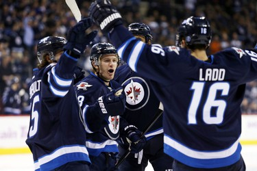 Winnipeg Jets forward Andrew Ladd (16) celebrates with teammates after he scores on Nashville Predators goalie Carter Hutton (30) (not shown) during the first period at MTS Centre.
