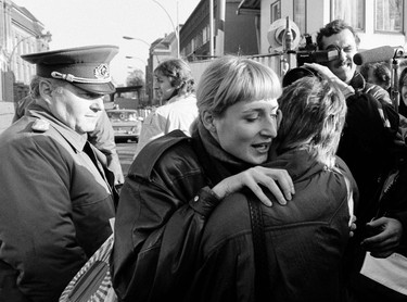 An East Berlin citizen (C) embraces a West Berlin woman while an East German border soldier watches at the border checkpoint Invalidenstrasse after the opening of the East German border was announced in Berlin, in this file picture taken November 10, 1989. (REUTERS/Fabrizio Bensch/Files)
