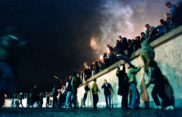 East German citizens climb the Berlin wall at the Brandenburg Gate after the opening of the East German border was announced in Berlin, in this file picture taken November 9, 1989. (REUTERS/Herbert Knosowki/Files)