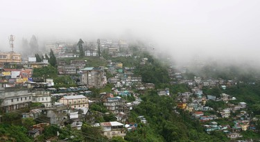 Clouds gather over Kurseong town near the eastern Indian hill town of Darjeeling, in this July 15, 2009 file photo. Darjeeling, for many people, means tea, but the eponymous hill resort nestled in the Himalayas in India's northeast is also a gateway to spectacular views of the world's third highest peak as well as a rare glimpse of snow leopards and red pandas. REUTERS/Rupak De Chowdhuri/Files