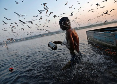 Photos of the week - A Hindu devotee takes a dip in the waters of the river Yamuna, an act that is considered to be holy, as part of prayers on the full moon day in the month of Karthik (also known as Karthik Purnima) in the early morning in New Delhi November 6, 2014. REUTERS/Ahmad Masood