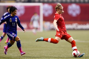 Canada midfielder Sophie Schmidt (13) passes back to a teammate against Japan forward Nahomi Kawashumi (11) during the second half at BC Place on Oct 28, 2014 in Vancouver, British Columbia, Canada. (Joe Nicholson/USA TODAY Sports)