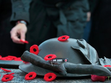 People lay poppies on the tomb of the unknown soldier at the National War Memorial to mark Canada's observance of Remembrance Day in Ottawa on Tuesday Nov 11,  2014.  Tony Caldwell/Ottawa Sun/QMI Agency