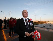 Minister of Veterans Affairs Julian Fantino handed out Canadian flags on the Jane Street overpass over Highway 407 after the procession of Cpl. Nathan Cirillo passed by, on Friday October 24, 2014. Stan Behal/QMI Agency