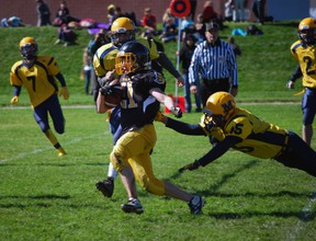 Central Elgin Collegiate Institute varsity football player Josh Butler (no. 21) streaks toward the end zone as Montcalm Cougars player Spencer Swan, right, tries to tackle him.  (File photo)